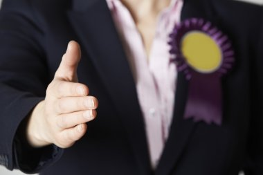Close Up Of Female Politician Reaching Out To Shake Hands