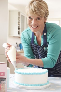 Woman Icing Birthday Cake In Kitchen At Home
