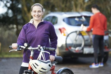 Couple Cycling Taking Mountain Bikes From Rack On Car