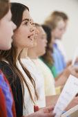 Iskolás gyermekek csoportja együtt énekelnek kórusban