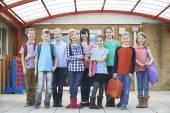 Porträt von Schülern außerhalb des Klassenzimmers, die Taschen tragen