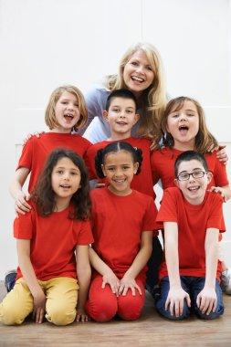 Group Of Children With Teacher Enjoying Drama Workshop Together