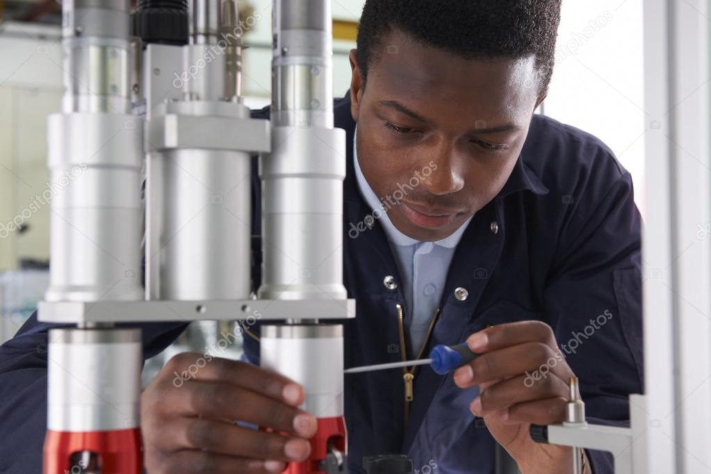 Male Apprentice Engineer Working On Machine In Factory