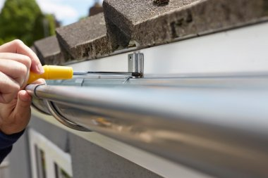 Close Up Of Man Replacing Guttering On Exterior Of House