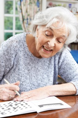 Senior Woman Relaxing With Crossword Puzzle At Home