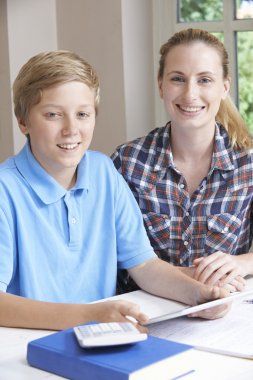 Female Home Tutor Helping Boy With Studies Using Digital Tablet