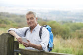 Senior férfi ellenőrzése a elhelyezés-val mozgatható telefon, kirándulás