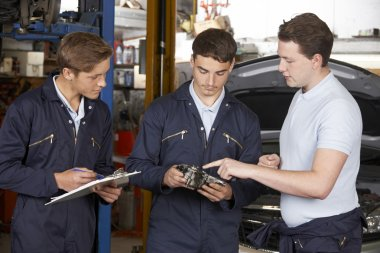 Mechanic Teaching Trainees In Garage Workshop