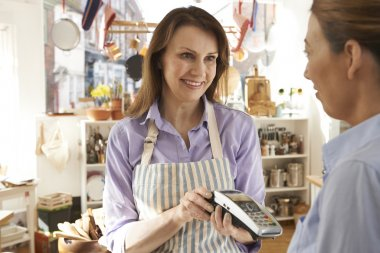 Customer Paying In Kitchen Shop Using Credit Card Terminal