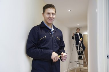 Electricians Installing Ceiling Lights In Domestic Home