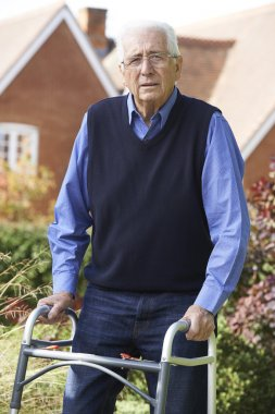 Senior Man In Garden Using Walking Frame