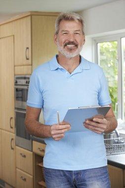 Builder Preparing Estimate For Home Improvement