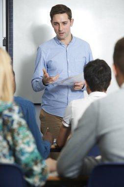Teacher Talking To Teenage Pupils In Class