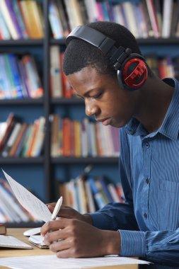 Male Teenage Student Working At Computer Wearing Headphones