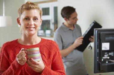 Woman Holding Mug Whilst Engineer Installs TV Equipment