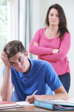 Frustrated Mother Watching Teenage Son Doing Homework