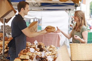 Customer Buying Loaf From Market Bread Stall