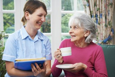 Senior Woman Being Visited By Carer At Home