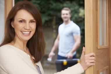 Woman Opening Door To Repair Man