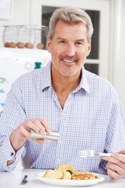 Man At Home Adding Salt To Meal