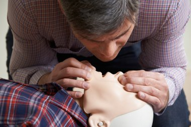 Man In First Aid Class Performing Mouth To Mouth Resuscitation O