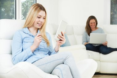 Teenage Girl Uses Digital Tablet Whilst Mother Works On Laptop
