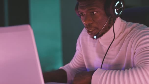Black man, workaholic with illuminated headset using laptop at night