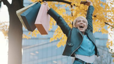 Happy young girl jumping with the shopping bags. Sales and discounts concept