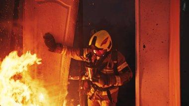 İtfaiyeci yanan evin kapısından giriyor..