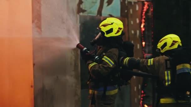 Zblízka, dva hasiči hasí požár, stříkající hadicí v noci.
