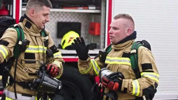 Dva hasiči potřásají rukou po úspěšném požárním cvičení