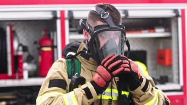 Feuerwehrmann entfernt Gasmaske aus dem Gesicht vor dem Feuerwehrauto
