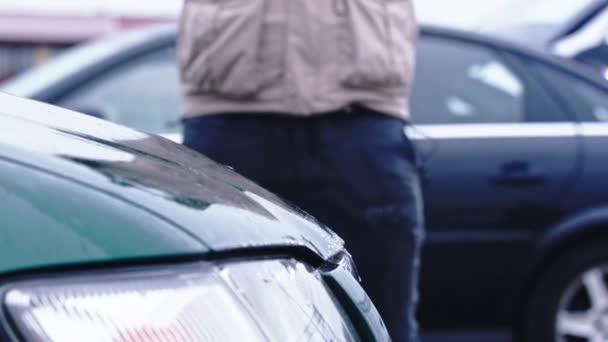Wütender Mann zertrümmert Auto mit großem Hammer Konzept von Terror und Vandalismus