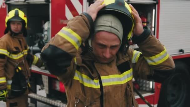 Portrét hasiče v plné uniformě a jeho doprovod před hasičským vozem