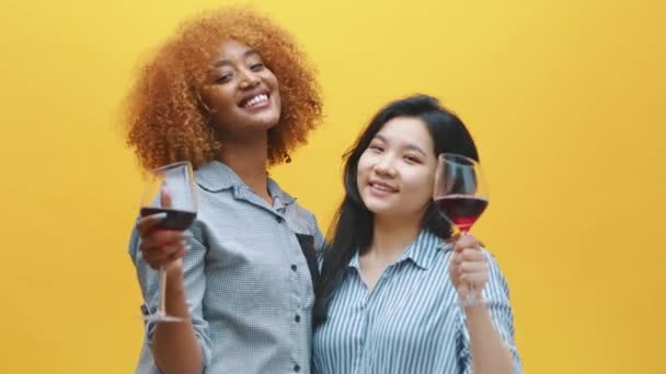 Young lesbian couple clinking glasses with red wine. Multiracial homosexual relationship, love and anniversary celebration concept