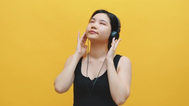 Portrait of happy asian young woman listening to the music on the headphones isolated on yellow background