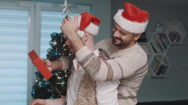 Karácsony a meleg családban. Boldog pasik ünneplik a karácsonyt öleléssel és ajándékokkal