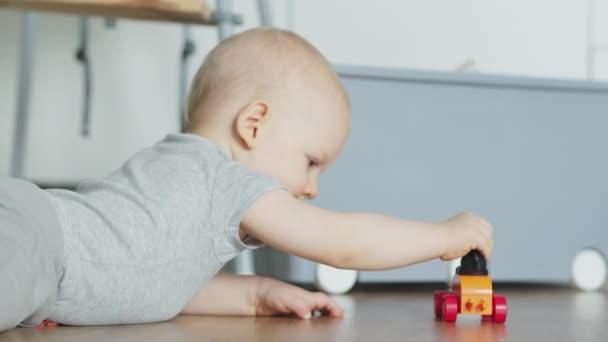 Rozkošný chlapeček hrající si s autíčkem na podlaze