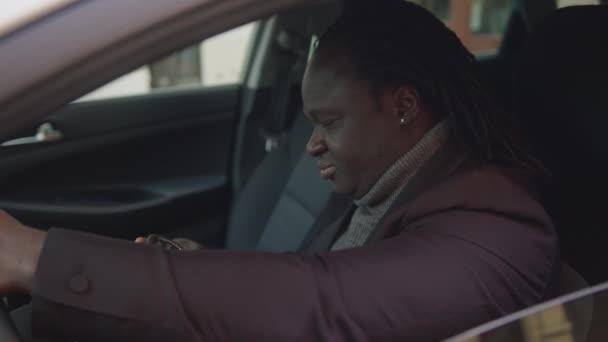 Erfolgreicher afrikanisch-amerikanischer Schwarzer zeigt Autoschlüssel, während er in seinem neuen Auto sitzt