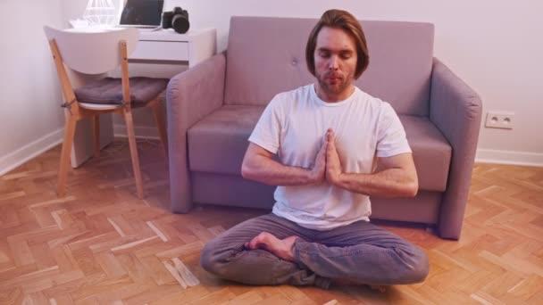 Junger bärtiger Mann meditiert in seiner Wohnung. Achtsamkeit und Konzept für psychische Gesundheit