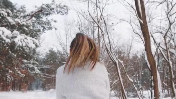Egy fiatal nő ugrált és havat szórt a fejére a parkban. Téli szezon