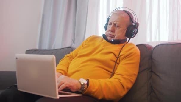 Glücklicher älterer Mann mit Headset beim Spielen auf dem Laptop