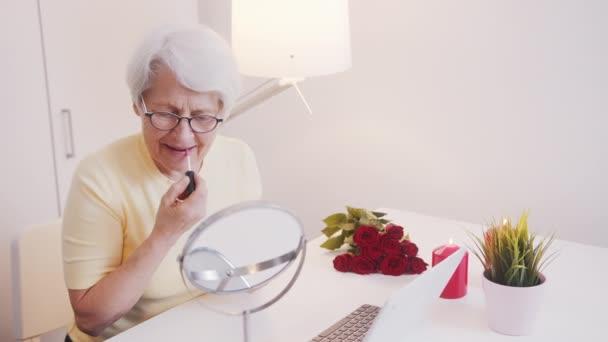 Ältere Frau, die Lippen glühen lässt. Reflexion im Spiegel. Valentinstag