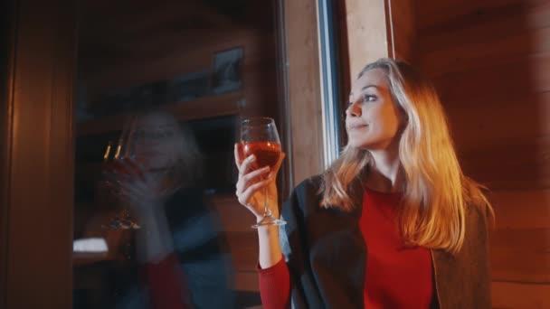 Junge blonde Frau trinkt Glühwein am Fenster und sieht Schnee fallen