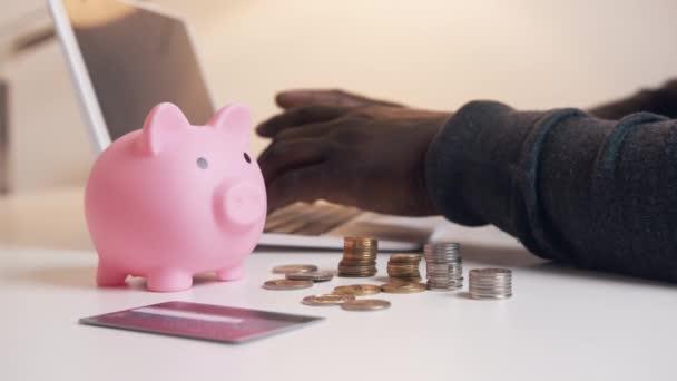 Ruce černochů pracujících na laptopu za prasaty a mincemi. Koncept účetnictví a financí