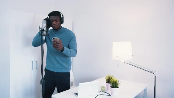 Férfi visel fejhallgató énekel egy dalt egy mikrofon a stúdióban - Fogása telefon