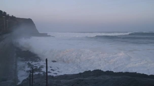 Huge waves crashing against a wall and splashing large amounts of water in form of foam