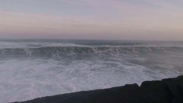 Giant waves with massive force crashing against the rocks at sunrise