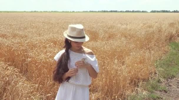 Žena v bílých šatech, stojící v poli drží uši pšenice