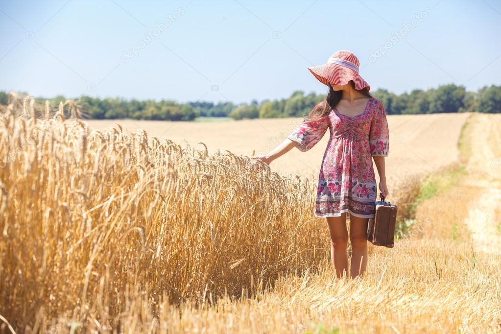 girl in hat on wheat field